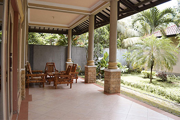 verandah with an outdoor setting overlooking the lush tropical gardens.